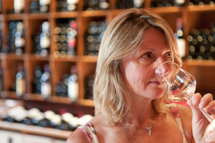 Woman smelling white wine in wine shopの写真素材 [FYI02116943]