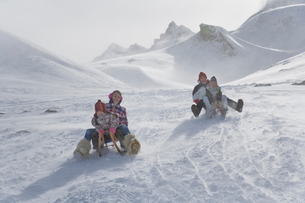 Young family sledding down mountain on winter dayの写真素材 [FYI02116949]
