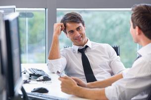 Smiling businessmen talking at desk in officeの写真素材 [FYI02116999]
