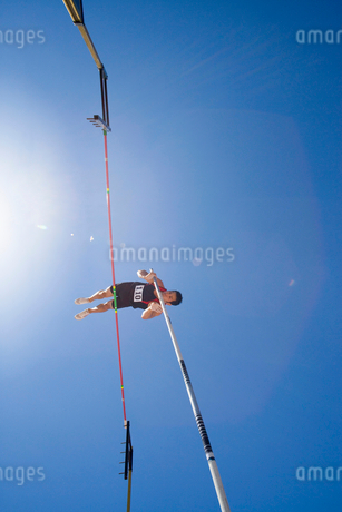 Pole vault athlete going over bar, low angle view (lens flare)の写真素材 [FYI02117041]