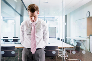 Dejected businessman leaning on glass window in conference roomの写真素材 [FYI02117042]