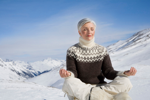 Mature woman doing yoga in mountains on winter dayの写真素材 [FYI02117045]