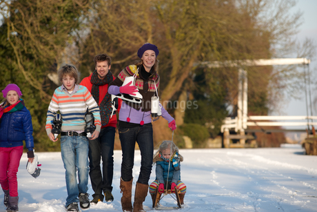 Family with ice skates and sled walking on winter dayの写真素材 [FYI02117076]