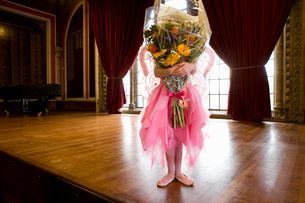 Ballerina girl (10-12) obscuring face with bunch of flowers onstageの写真素材 [FYI02117084]