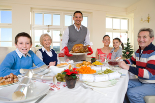 Multi-generation family eating Christmas dinner at dining room tableの写真素材 [FYI02117095]
