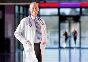 Smiling doctor in lab coat standing in hospital hallwayの写真素材 [FYI02117110]