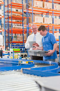 Supervisor and worker examining machine parts in bin on production line in distribution warehouseの写真素材 [FYI02117117]