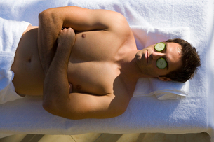 Bare chested man having beauty treatment, cucumber slices on eyes, elevated viewの写真素材 [FYI02117122]