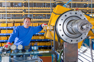 Portrait of smiling engineer leaning on machinery in factoryの写真素材 [FYI02117130]