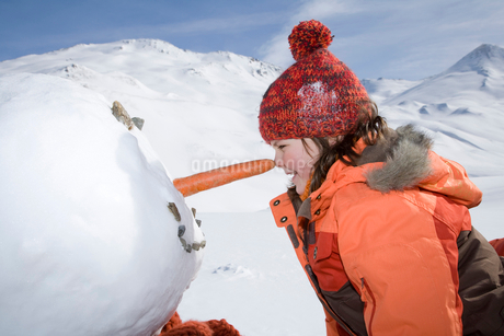 Young girl rubbing nose against snowman with a carrot noseの写真素材 [FYI02117131]