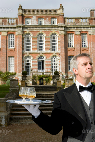 Mature butler with drinks on tray by manor house, close-upの写真素材 [FYI02117138]