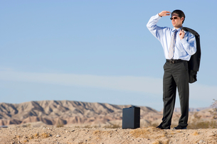 Businessman in sunglasses with briefcase in desert, looking into distanceの写真素材 [FYI02117139]