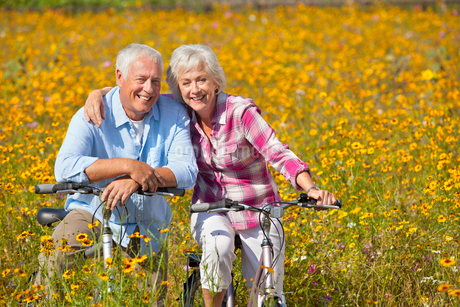 Portrait of smiling couple on bicycles among wildflowers in sunny meadowの写真素材 [FYI02117170]