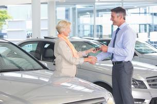 Salesman and customer shaking hands in car dealership showroomの写真素材 [FYI02117173]