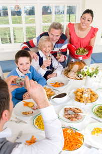 Multi-generation family eating dinner at dining room tableの写真素材 [FYI02117179]
