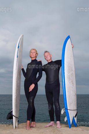 Male and female surfers in wetsuits with surfboards by beachの写真素材 [FYI02117196]