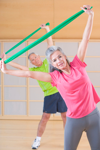 Portrait of senior man and woman exercising with resistance bands in gymの写真素材 [FYI02117201]