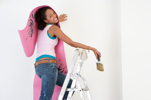 Young woman on ladder putting up wallpaper, smiling, portraitの写真素材 [FYI02117217]