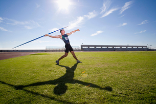 Male athlete preparing to throw javelin, low angle view (lens flare)の写真素材 [FYI02117222]