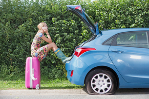 Woman With Flat Tyre On Car Phoning For Assistanceの写真素材 [FYI02117270]
