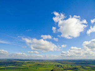 Scenic aerial view of green rolling landscape under sunny blue sky with cloudsの写真素材 [FYI02117276]