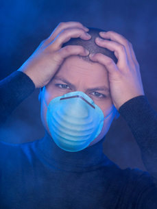 Mid adult man wearing surgical mask in smoke filled room, studio shotの写真素材 [FYI02117286]
