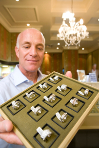 Mature male jewellery shop assistant with tray of rings, smilingの写真素材 [FYI02117291]