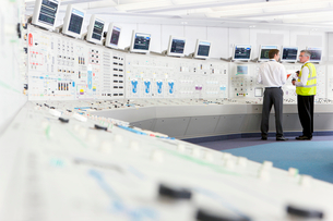 Engineers at control panel in control room of nuclear power stationの写真素材 [FYI02117304]