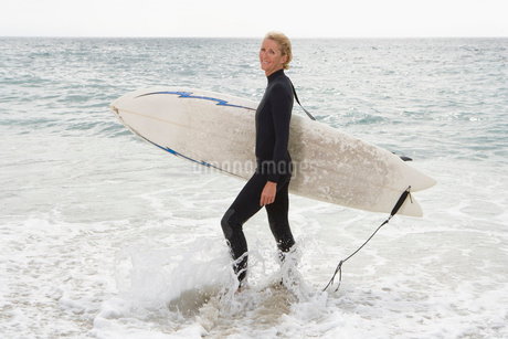 Female surfer in shallow water on beachの写真素材 [FYI02117314]