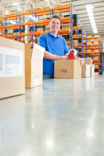 Portrait of smiling worker taping cardboard boxes on production line in distribution warehouseの写真素材 [FYI02117325]