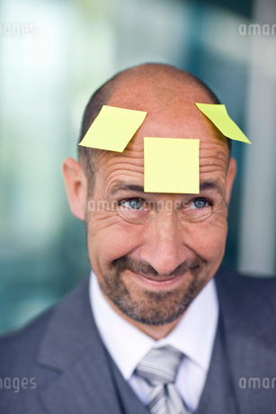 Portrait of mature man with three note papers stuck on foreheadの写真素材 [FYI02117326]