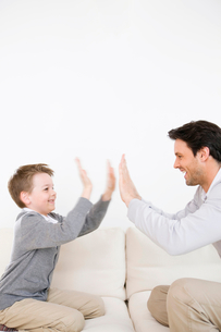 Father and son giving each other high fivesの写真素材 [FYI02117335]