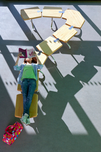 Student laying on row of school desks formed into a question mark symbol studyingの写真素材 [FYI02117360]