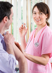 Nurse holding syringe and preparing to give man an injectionの写真素材 [FYI02117367]
