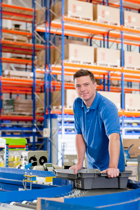 Portrait of confident worker with bin on production line in distribution warehouseの写真素材 [FYI02117375]