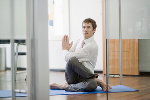 A businessman practicing yoga in his officeの写真素材 [FYI02117378]