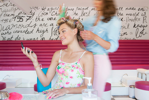 Hairdresser spraying hairspray on curlers in woman's hair at salonの写真素材 [FYI02117380]