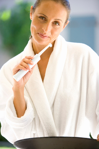 Woman in bathrobe brushing teeth with electric toothbrush, smiling, portraitの写真素材 [FYI02117396]