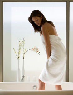 A young woman standing in a bathの写真素材 [FYI02117398]