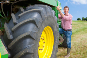 Portrait of smiling farmer climbing into tractor in fieldの写真素材 [FYI02117400]