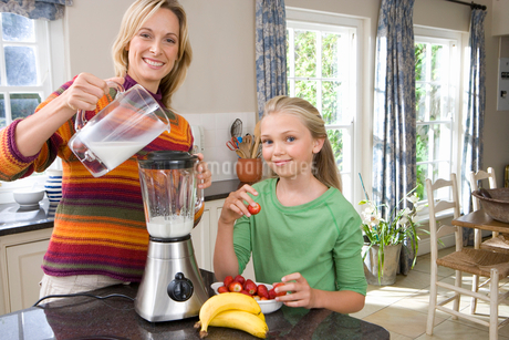 Mother and daughter (8-10) making banana and strawberry smoothie, smiling, portraitの写真素材 [FYI02117409]