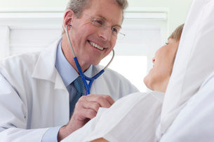 Doctor listening to patient's heartbeat in hospital roomの写真素材 [FYI02117440]