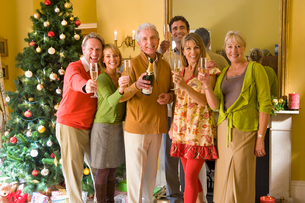 Family by Christmas tree proposing toast with champagne, smiling, portraitの写真素材 [FYI02117441]