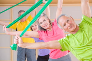 Portrait of senior people exercising with resistance bands in gymの写真素材 [FYI02117451]