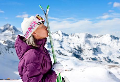 Woman kissing skis on snowy mountainの写真素材 [FYI02117460]