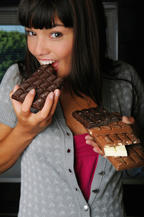 Portrait of young woman eating chocolate barsの写真素材 [FYI02117475]