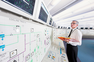 Engineer looking up at monitors in control room of nuclear power stationの写真素材 [FYI02117518]