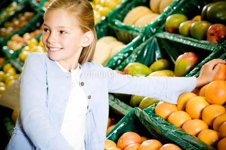 Portrait of a young girl holding two grapefruits in a supermarketの写真素材 [FYI02117525]