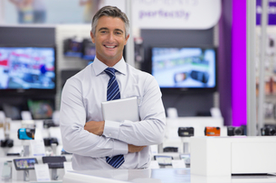 Portrait of smiling salesman holding digital tablet in electronics storeの写真素材 [FYI02117528]
