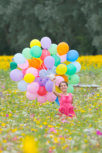Portrait of smiling girl holding bunch of balloons among wildflowers in sunny meadowの写真素材 [FYI02117536]
